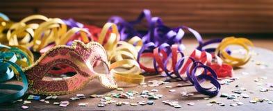 Partido del carnaval Máscara, confeti y serpentinas en fondo de madera Foto de archivo