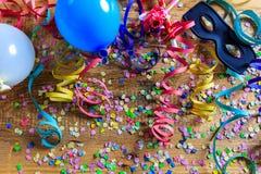 Partido del carnaval Máscara, confeti y serpentinas en piso de madera Fotos de archivo