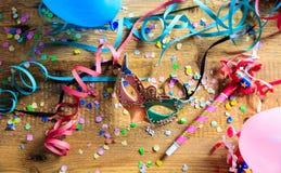 Partido del carnaval Máscara, confeti y serpentinas en piso de madera Foto de archivo libre de regalías