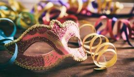 Partido del carnaval Máscara y serpentinas en fondo de madera Fotografía de archivo