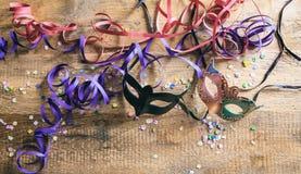 Partido del carnaval Máscaras, confeti y serpentinas en el fondo de madera, niew superior Fotografía de archivo libre de regalías