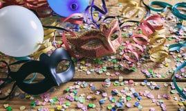 Partido del carnaval Máscaras, confeti y serpentinas en piso de madera Fotografía de archivo libre de regalías