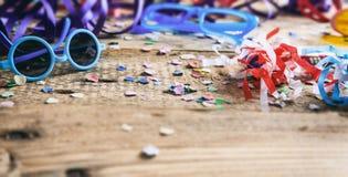 Partido del carnaval Vidrios, confeti y serpentinas en fondo de madera Fotos de archivo