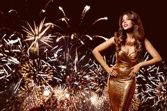 Partido del fuego artificial de la mujer, modelo de moda Celebrating en vestido de oro imagenes de archivo