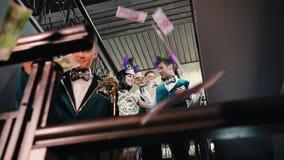 Partido del tema - gente joven en la ropa que relucir elegante que va abajo con las bebidas en sus manos - el caer del dinero metrajes