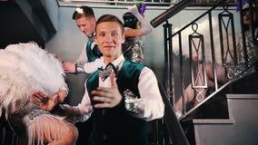 Partido del tema - gente joven en la ropa retra que relucir elegante que se coloca en las escaleras y que muestra apagado sus tra metrajes
