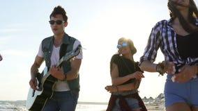 Partido del verano en la playa Muchachos jovenes y muchachas que aplauden, bailando junto tocando la guitarra y cantando cancione metrajes