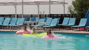 Partido del verano, muchachas que descansan por el poolside con el colchón y anillo inflable, novias en salto del bañador almacen de video