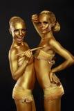 Partido del vestido de lujo. Pares de mujeres con la piel pintada metálica de oro. Creatividad Foto de archivo