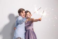Partido, divertimento e conceito dos feriados - par feliz novo com os chuveirinhos no fundo branco fotos de stock