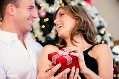 Partido: El hombre sorprende a la mujer con el pequeño regalo de la Navidad imágenes de archivo libres de regalías