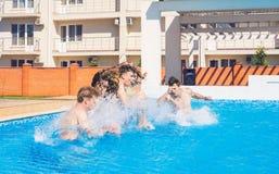 Partido en la piscina smimming Grupo de amigos alegres que saltan en el agua Imágenes de archivo libres de regalías