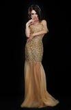 Partido formal Modelo de moda atractivo en vestido de oro elegante sobre negro Foto de archivo