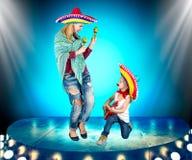 Partido mexicano Um menino pequeno em um sombreiro joga a guitarra e canta uma serenata para sua mãe imagens de stock