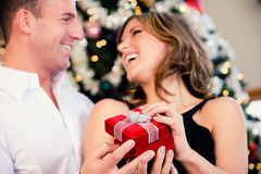 Partido: O homem surpreende a mulher com o presente pequeno do Natal imagens de stock royalty free