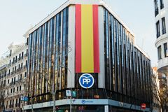 Partido popular building at Génova 13 and big Spanish flag on the facade. PP logo stock photo