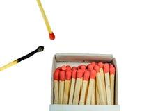 Partido quemado y caja de cerillos roja del partido y abierta aislada en un fondo blanco imagenes de archivo