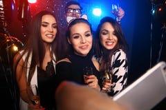 Partido, tecnología, vida nocturna y concepto de la gente - amigos sonrientes con el smartphone que toma el selfie en club Imagenes de archivo