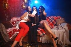 Partido, tecnología, vida nocturna y concepto de la gente - amigos sonrientes con el smartphone que toma el selfie en club Fotografía de archivo