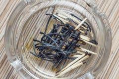 Partidos quemados en un cenicero de cristal en textura de madera del fondo Fotos de archivo libres de regalías