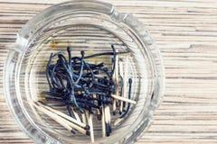 Partidos quemados en un cenicero de cristal en textura de madera del fondo Fotografía de archivo libre de regalías