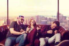 Partie à la maison, amis s'asseyant sur le divan et rire Photographie stock libre de droits
