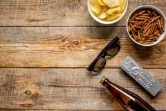 Partie à la maison avec l'observation, les casse-croûte et la bière de TV sur la moquerie en bois de vue supérieure de fond  Photographie stock libre de droits