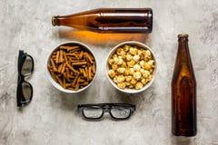 Partie à la maison avec l'observation, les casse-croûte et la bière de TV sur la vue supérieure de fond en pierre Photographie stock