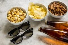 Partie à la maison avec l'observation, les casse-croûte et la bière de TV sur le fond en pierre Photos libres de droits