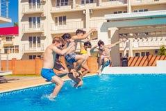 Partie à la piscine smimming Groupe d'amis gais sautant dans l'eau Photographie stock libre de droits