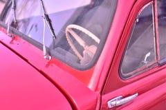 Partie antérieure de plan rapproché de la rétro voiture rouge sur la rue de ville photos libres de droits