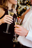Partie : Couples grillant avec Champagne By Christmas Tree Image stock