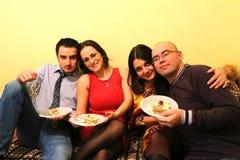 Partie d'amis à la maison : Consommation du gâteau Photo stock