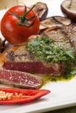 Partie de bifteck rare moyen avec de la sauce épicée à herbe Photos stock