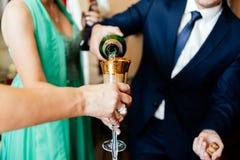 Partie de Champagne L'homme dans le costume verse le champagne dans un verre Images libres de droits