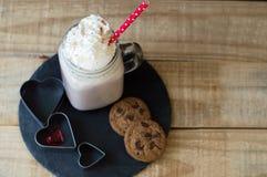 Partie de chocolat chaud avec l'écrimage crème fouetté et le stra rouge Image stock