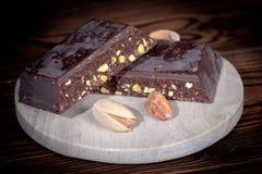 partie de chocolat foncé avec l'écrou des pistaches sur la table image stock