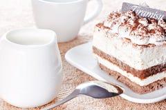 Partie de dessert de tiramisu et d'une cuvette de café Image stock