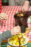 Partie de fondue de chocolat sucré de dessert avec des cubes de pommes, de poires, d'ananas et de raisins Photo stock