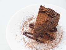 Partie de gâteau de chocolat de la plaque blanche La tranche de 'brownie' frais a arrangé du plat blanc photographie stock libre de droits
