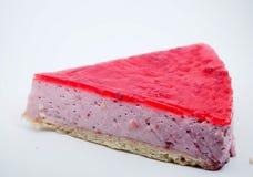 Partie de gâteau sur le fond blanc Gâteau au fromage avec la gelée de framboise photo libre de droits