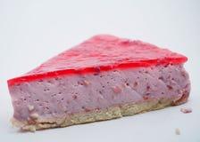 Partie de gâteau sur le fond blanc Gâteau au fromage avec la gelée de framboise images libres de droits