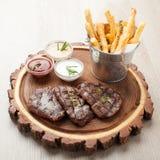 Partie de mignon de filet de boeuf de BBQ avec des sauces et les pommes de terre frites Images stock