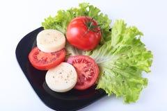 Partie de mozzarella avec les tomates, la feuille de laitue et le habillage balsamique du plat noir tir de plan rapproché de foye Photos stock