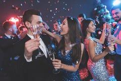 Partie de nouvelle année Jeune danse de couples avec des verres de champagne dans des mains Images stock