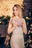 Partie de nouvelle année, vacances Belle jeune femme dans le sac d'or de robe et d'embrayage en main sur le fond de décoration de photo stock