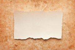 Partie de papier déchirée sur le fond de papier grunge Images stock