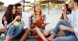 Partie de plage avec des amis Les jeunes gais passant le temps gentil ensemble sur la plage Image stock