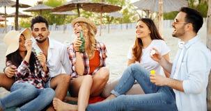 Partie de plage avec des amis Les jeunes gais passant le temps gentil ensemble sur la plage Images libres de droits