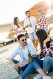 Partie de plage avec des amis Les jeunes gais passant le temps gentil ensemble sur la plage Photos libres de droits